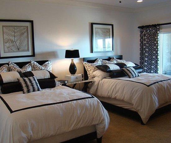 空间较小的空间用来打造客卧十分不错,为了营造温馨感,用浅色原木色与与其接近的裸色及驼色来打造:木制床架、书柜以及木墙、裸色窗帘、驼色地毯,清新而淡雅。特别挑选的圆形吊灯,用柔和的光与美丽的造型进一步提升了空间的品质。    客卧被设置在了阁楼之上,很好的利用了闲置的大空间,靠窗的位置正好摆入白色铁艺大床,特地选用了蓝色调布艺:床品以及条纹地毯,增添清爽感的同时,条纹又能在视觉上伸展空间。靠外位置还增添了卫浴设备,增添了阁楼客卧的便捷性。    处于小空间里的客卧,家具的摆放采用靠墙的设计,窗户旁边的