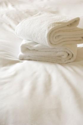 酒店床单上的白色毛巾高清图片图片